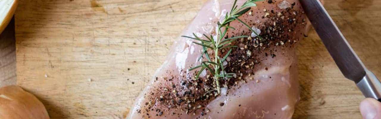 Raw chicken seasoned on cutting board