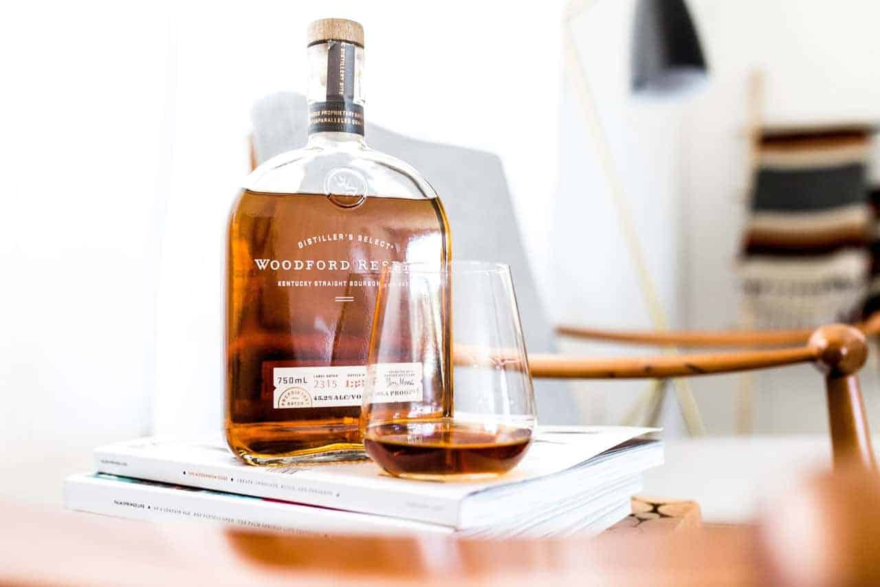 Bottle of bourbon with glass by chair